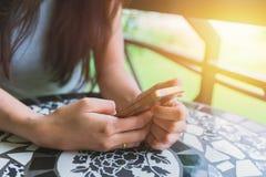 Mano della ragazza che si siede facendo uso del touch screen dello smartphone fotografie stock libere da diritti