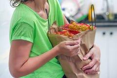 Mano della ragazza con le borse di alimento a casa fotografia stock