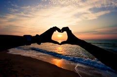Mano della siluetta nella forma del cuore Fotografia Stock