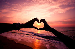 Mano della siluetta nella forma del cuore Fotografie Stock