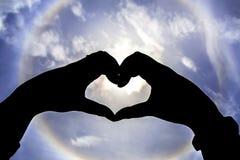 Mano della siluetta nella forma del cuore Immagini Stock Libere da Diritti