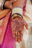 Mano della sposa con hennè ed i braccialetti fotografia stock