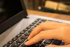 Mano della studentessa asiatica che lavora ad un computer portatile ad una caffetteria Fotografia Stock