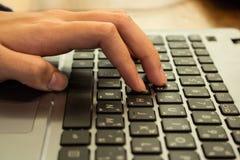 Mano della studentessa asiatica che lavora ad un computer portatile ad una caffetteria Fotografie Stock