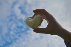Mano della tenuta dell'uomo fino al cielo sotto forma del cuore di amore con cuore sul chiarore e sulla nuvola di luce solare del fotografia stock