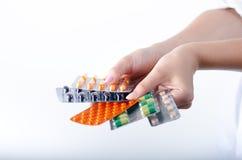 Mano della tenuta femminile di medico pillole Priorità bassa della farmacia Tipo differente di pillole in bolle Pillole Medicina  Immagini Stock