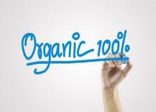 Mano delle donne che scrive 100% organico sul fondo grigio per l'affare Immagine Stock