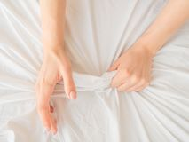 Mano delle donne che tirano gli strati bianchi bedroom Chiuda sulla vista immagine stock