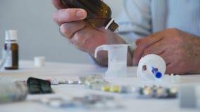 Mano delle droghe di gocciolamento dell'uomo anziano nel becher video d archivio