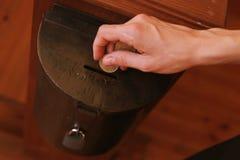 Mano delle monete di lancio di una giovane donna in una scatola di donazione Concetto di donazione immagine stock