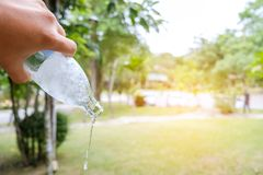 Mano delle persone che tiene una bottiglia di acqua che se lo immerge in fuori in giardino, Fotografia Stock