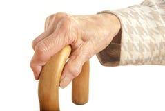 Mano delle signore anziane con il bastone da passeggio immagine stock