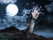Mano dello zombie che esce dalla sua tomba Fotografie Stock