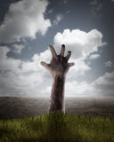 Mano dello zombie che esce dalla sua tomba Fotografia Stock Libera da Diritti