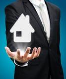 Mano derecha de la postura del hombre de negocios que lleva a cabo el icono de la casa aislado Fotos de archivo
