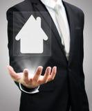 Mano derecha de la postura del hombre de negocios que lleva a cabo el icono de la casa aislado Imagen de archivo