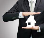 Mano derecha de la postura del hombre de negocios que lleva a cabo el icono de la casa aislado Imagenes de archivo