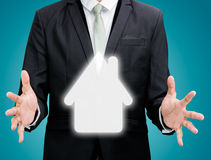 Mano derecha de la postura del hombre de negocios que lleva a cabo el icono de la casa aislado Imágenes de archivo libres de regalías