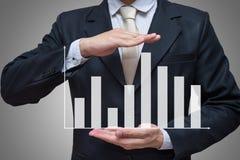 Mano derecha de la postura del hombre de negocios que lleva a cabo finanzas del gráfico aisladas en fondo gris Foto de archivo