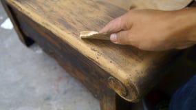Mano derecha usando el papel de lija para la restauración de madera Imagen de archivo