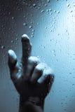 Mano detrás de la ventana mojada Imagenes de archivo