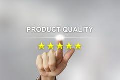 Mano di affari che spinge qualità del prodotto sullo schermo immagini stock