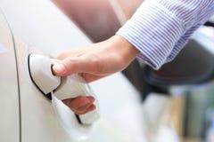 Mano di affari sulla maniglia Femmina del primo piano che apre una porta di automobile Immagini Stock
