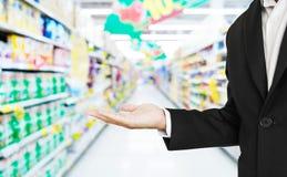 Mano di allungamento dell'uomo d'affari con il fondo della navata laterale del supermercato di defocus Fotografie Stock Libere da Diritti