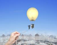 Mano di camminata della donna della corda per funamboli dell'uomo d'affari che tira lampadina a calda Fotografia Stock