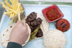 Mano di Childs che prende le patate fritte dal piatto Fotografia Stock
