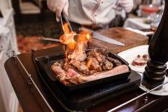 Mano di grigliare una certe carne e polpetta sulla fiamma calda Immagine Stock Libera da Diritti
