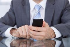 Mano di Holding Cellphone In della persona di affari fotografie stock libere da diritti