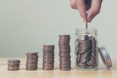 Mano di maschio o della femmina che mette le monete in barattolo con la stanza della pila dei soldi Fotografie Stock Libere da Diritti