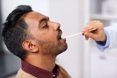 Mano di medico che esamina gola paziente alla clinica Immagine Stock