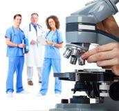 Mano di medico con il microscopio Fotografie Stock Libere da Diritti