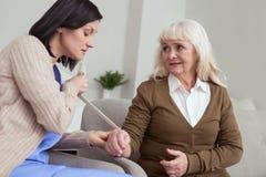 Mano di riparazione preoccupata della donna più anziana dell'infermiere con la fasciatura Immagine Stock Libera da Diritti
