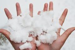 Mano di s della neve della tenuta ' Fotografia Stock