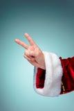 Mano di Santa Claus che mostra vittoria del segno con i pollici su Fotografia Stock