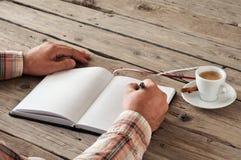Mano di scrittura dell'uomo qualcosa in taccuino in bianco sulla tavola di legno Fotografie Stock Libere da Diritti