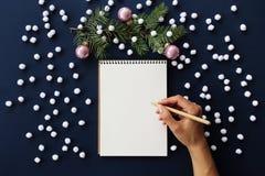 Mano di scrittura in taccuino, decorazioni di Natale Fotografie Stock Libere da Diritti
