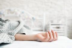 Mano di sonno a letto primo piano coperto della donna Immagini Stock Libere da Diritti