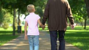 Mano di tenuta di prima generazione del nipote, camminante insieme, supporto durante la vita video d archivio