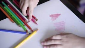 mano di un bambino che disegna un cuore rosso della matita su una cartolina casalinga Istruzione del ` s dei bambini video d archivio