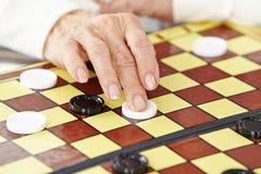 Mano di un gioco senior della donna Fotografia Stock