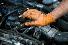 Mano di un meccanico su un motore di automobile Fotografia Stock Libera da Diritti