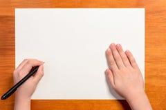 Mano di un ragazzino con una penna nera su un fondo bianco fotografia stock