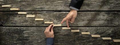 Mano di un uomo d'affari che sostiene un punto di legno per il suo collega Fotografia Stock