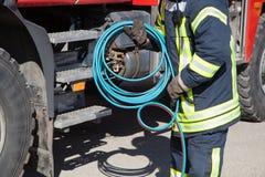 Mano di un vigile del fuoco che collega un firehose ad uno sbocco. Immagini Stock Libere da Diritti