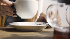 Mano di una donna caucasica con chiodi neri che toccano una tazza di tè bianco seduta al caffè Giovane donna rilassante video d archivio