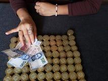 mano di una donna che tiene le banconote messicane e le monete impilate di dieci pesi messicani immagine stock